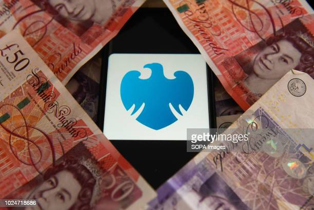 Fifty and twenty pounds bank notes and Barclays bank logo are seen in this photo illustration.