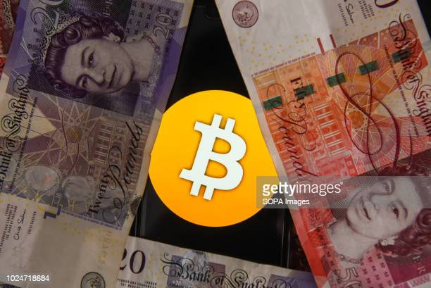 Fifty and twenty pounds bank notes and bitcoin logo are seen in this photo illustration.