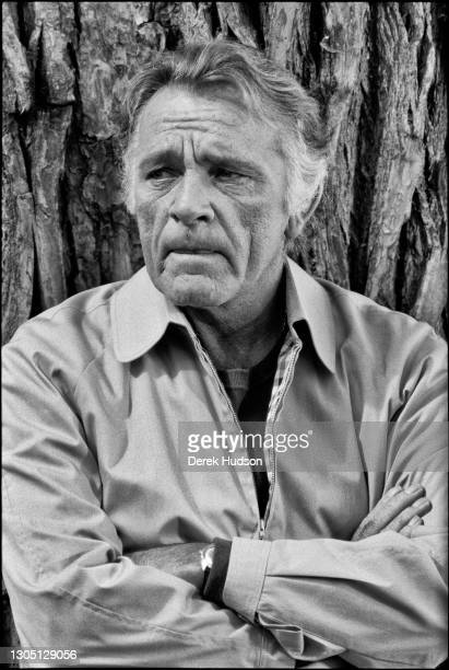Fifty four year old Welsh actor, Richard Burton pictured leaning against the bark of a tree trunk, arms folded wearing a zip-up casual bomber jacket...