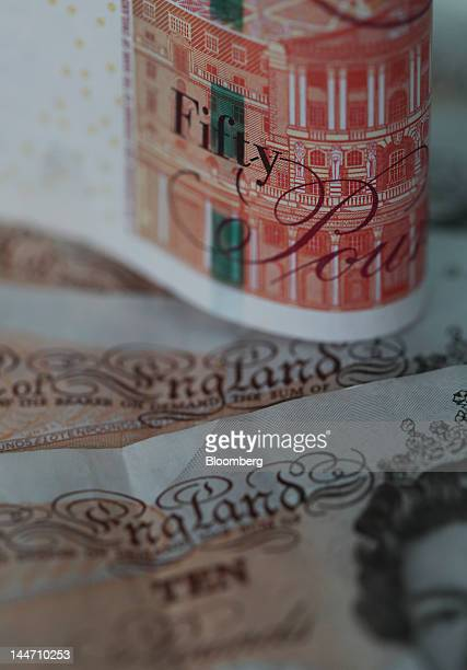 A fifty pound note sits with a set of ten pound notes in this arranged photograph in London UK on Thursday May 17 2012 UK Prime Minister David...