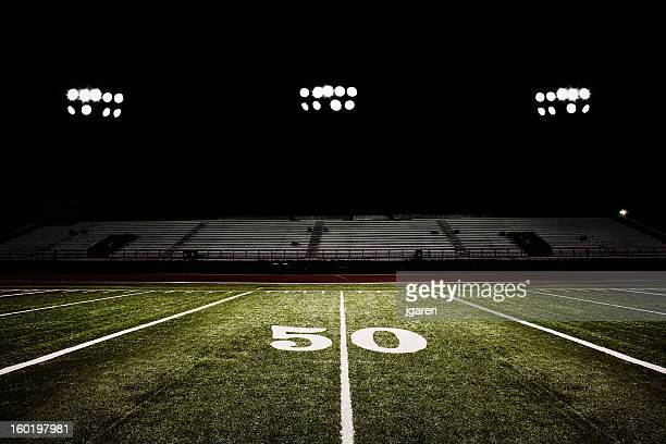 fifty-yard line of football field at night - empty bleachers stockfoto's en -beelden