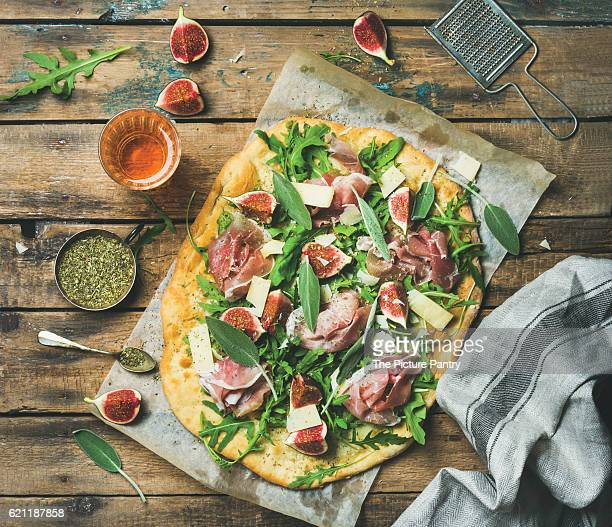 Fig, prosciutto, arugula and sage flatbread pizza with glass of rose wine on wax paper over rustic wooden background