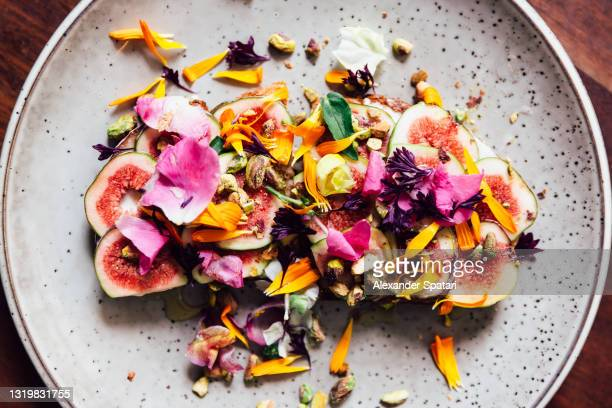 fig toast with edible flowers, directly above view - luxury stock pictures, royalty-free photos & images