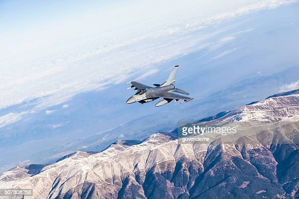 Figher jet flying over the mountains