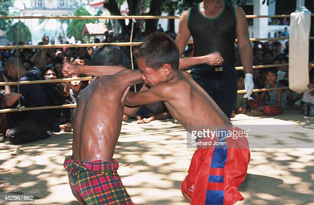A fight between a young Thai and a Burmese boxer at a Buddhist temple in Mae Kon Ken village close to the ThaiBurmese border Adult bouts have five...