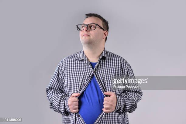 fight for people with disabilities , young happy man with down syndrome undoing his shirt like superman on studio background - intellectually disabled stock pictures, royalty-free photos & images