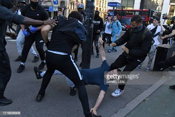TOPSHOT A fight takes place near Waterloo Station as protesters supporting the Black Lives Matter movement clash with opponents in central London on...