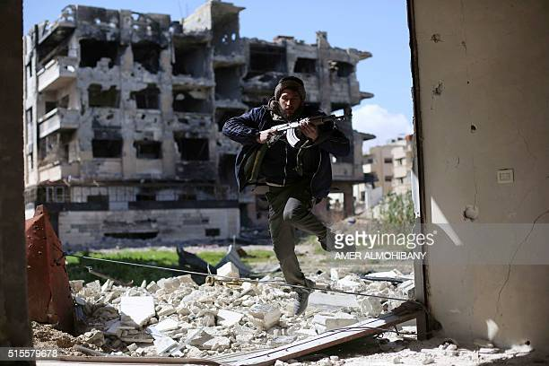 TOPSHOT A fighter belonging to Jaish alIslam runs to take cover near the frontline on March 14 2016 in the neighbourhood of Jobar on the eastern...