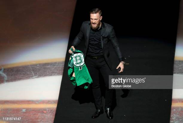 9d8c900c3fd MMA fighter Conor McGregor holds a green Bruins jersey as he comes out for  the ceremonial