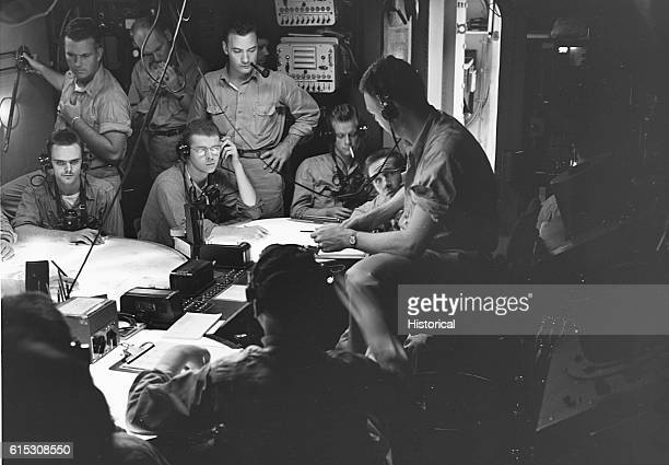 Fighter director Lt Comdr A F Fleming and radarmen supervise air combat patrols during a strike on the Marshall and Gilbert islands from the air plot...