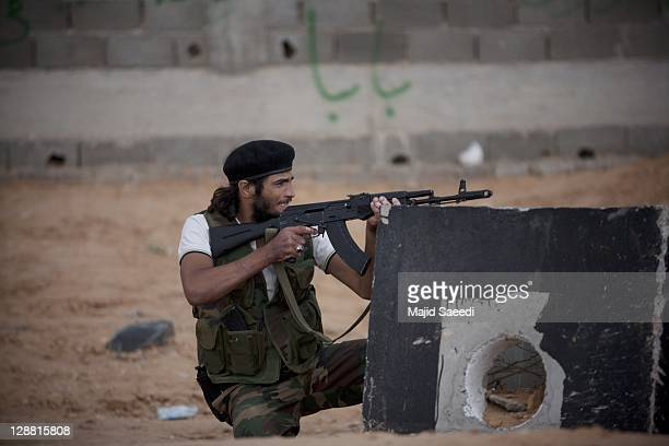 Fighter fires from cover on October 7, 2011 in Sirte, Libya. National Transitional Council fighters say this is the final assault on Muammar...