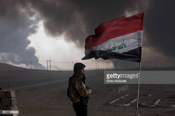 A fighter from a local tribe keeps watch from his rooftop outpost under smoke filled skies from burning oil wells set on fire by fleeing ISIS members...