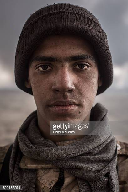 A fighter from a local tribe poses for a portrait at his rooftop outpost under smoke filled skies from burning oil wells set on fire by fleeing ISIS...