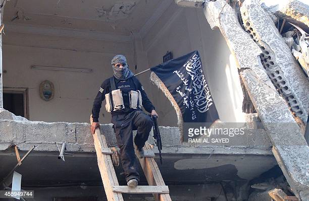 A fighter from the alQaida group in the Levant AlNusra Front carrying the movements flag climbs down from a destroyed building near the front line...