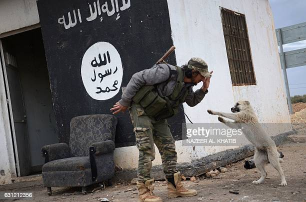 Fighter from the Free Syrian Army plays with a dog at a checkpoint which they've captured from Islamic State group jihadists near the town of...