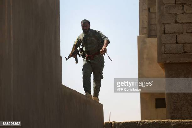 A fighter from the Hashed alShaabi backing the Iraqi forces takes position as troops advance through Tal Afar's alWahda district during an operation...