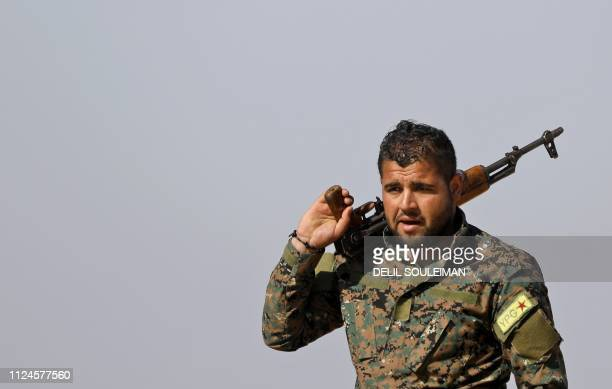 Fighter from the Kurdish People's Protection Units , part of the of the Syrian Democratic Forces , holds a Kalashnikov assault rifle on his shoulder...
