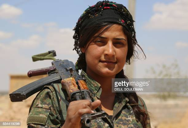 A fighter from the Kurdish People's Protection Units part of the Syrian Democratic Forces holds her weapon in the village of Fatisah in the northern...