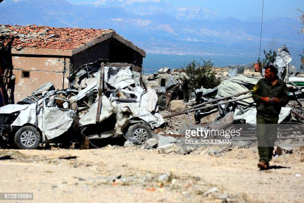 A fighter from the Kurdish People's Protection Units visits the site of Turkish airstrikes near northeastern Syrian Kurdish town of Derik known as...