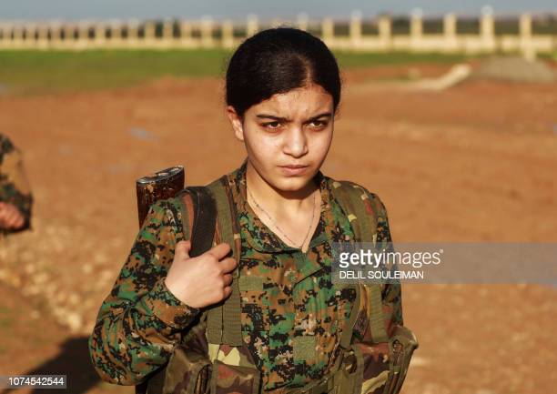 A fighter from the Kurdish women's protection units attends the funeral of an Arab fighter of the Syrian Democratic Forces in the town of Tal Tamr in...