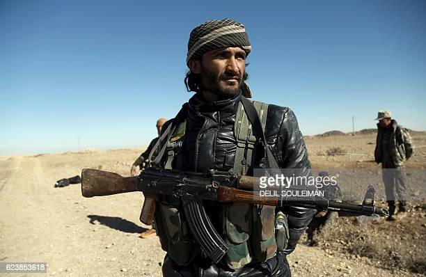 TOPSHOT A fighter from the KurdishArab alliance known as the Syrian Democratic Forces on Raqa advances in the village of Tall as Samn near the front...