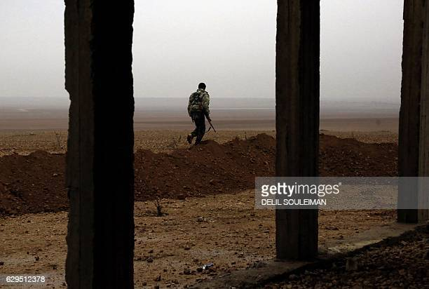CORRECTION A fighter from the KurdishArab alliance known as the Syrian Democratic Forces walks near the village of Khirbet alJahshe some 35...