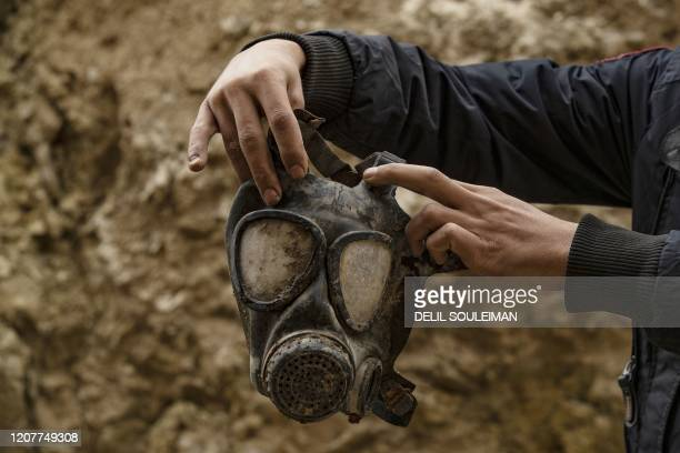 TOPSHOT A fighter from the Syrian Democratic forces carries a gas mask said to have belonged to Islamic State group jihadists recovered in the...