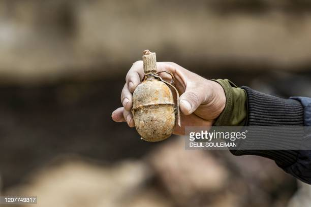 TOPSHOT A fighter from the Syrian Democratic forces carries a grenade said to have belonged to Islamic State group jihadists recovered in the eastern...