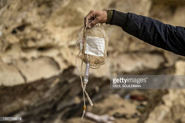TOPSHOT A fighter from the Syrian Democratic forces carries an empty anticoagulant solution bag attached to a needle for intravenous use said to have...