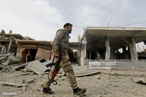 A fighter from the Syrian Democratic Forces walks past a former Islamic State group jihadist alms tax centre in the city of Hajin in Syria's eastern...