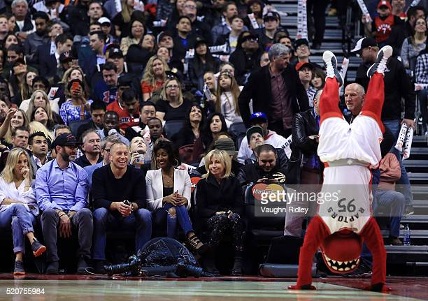 MMA fighter George St Pierre laughs as The Toronto Raptors mascot The Raptor tries to impress him during a break in the second half of an NBA game...