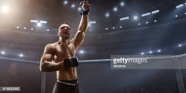 MMA fighter in professional boxing ring emotionally rejoices in victory