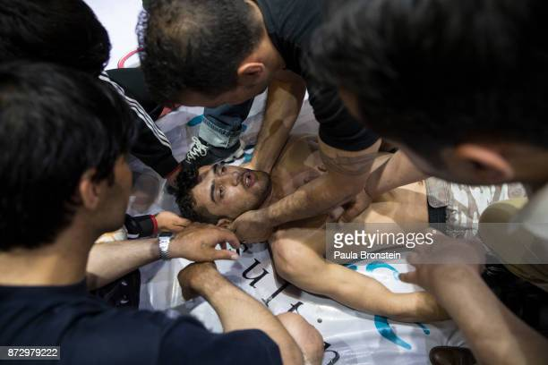 A fighter is physically checked out after he gets knocked down during the first round at the Snow Leopard Fighting Championship ring amateur event on...