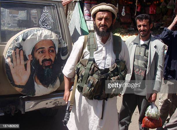 A fighter is seen standing in front of an image of Osama bin Laden the late head of alQaeda in the town of Rada 130 kilometres southeast of the...