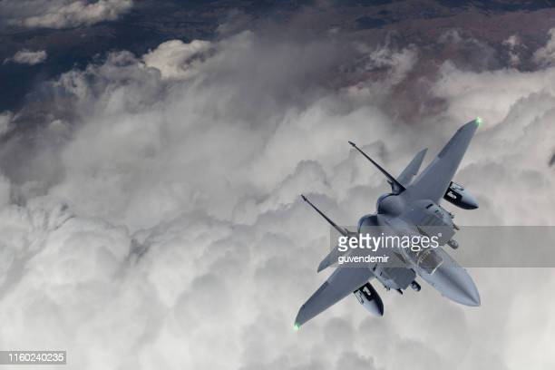 f-15 fighter jet flying over clouds - military airplane stock pictures, royalty-free photos & images