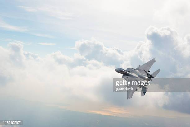 f-15 fighter jet flying over clouds - defending stock pictures, royalty-free photos & images