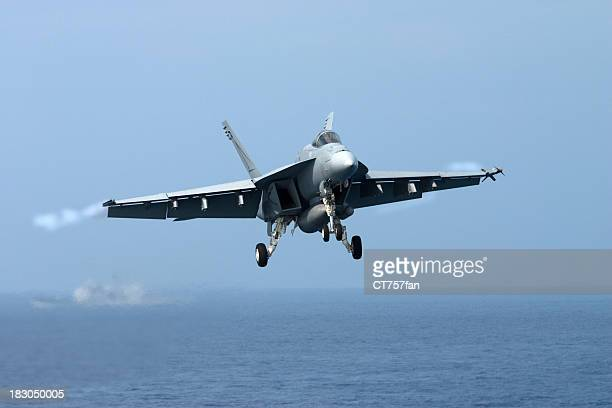 a fighter jet in the air over the sea - us navy stock pictures, royalty-free photos & images