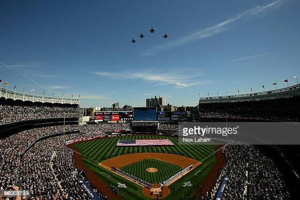 Fighter jets fly over as recording artist Kelly Clarkson sings the National Anthem while members of the military hold a giant American flag before...