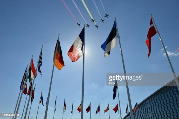 Fighter jets fly over flags during the NATO summit ceremony at the NATO summit ceremony at the NATO headquarters on May 25 2017 in Brussels Belgium