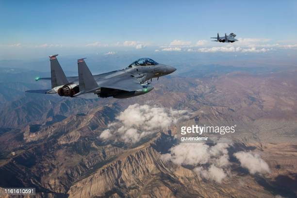 f-15 fighter jets flying over mountains - us military stock pictures, royalty-free photos & images
