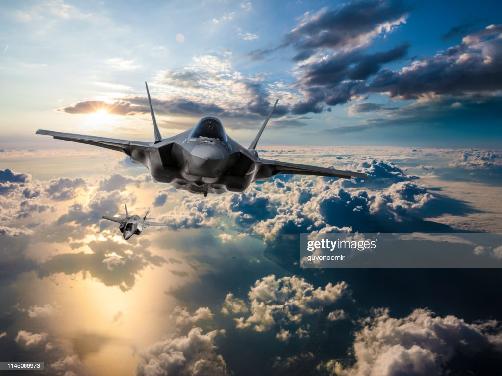 F-35 Fighter Jets flying over the clouds at sunset : Stock Photo