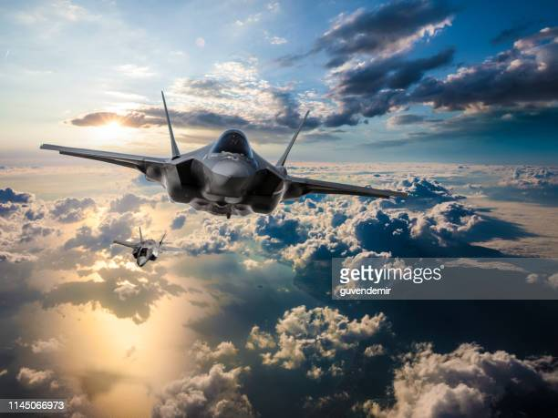 f-35 fighter jets flying over the clouds at sunset - military stock pictures, royalty-free photos & images