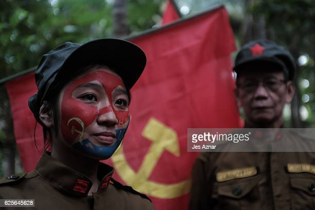 Fighter Katryn and DIego standing next to a communist flag inside their camp on November 23, 2016 in Sierra Madre, Philippines. The New People's...