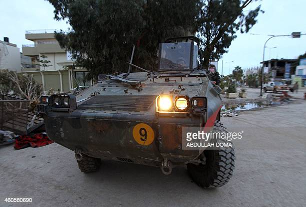 A fighter loyal to Khalifa Haftar a retired general and former chief of staff for Moamer Kadhafi drives a miliatary vehicle as they fight alongside...