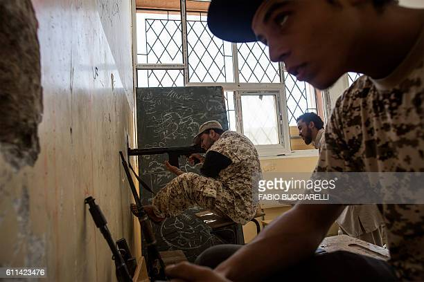 TOPSHOT A fighter loyal to Libya's Government of National Accord fires his weapon from a former school on the western frontline towards Islamic State...