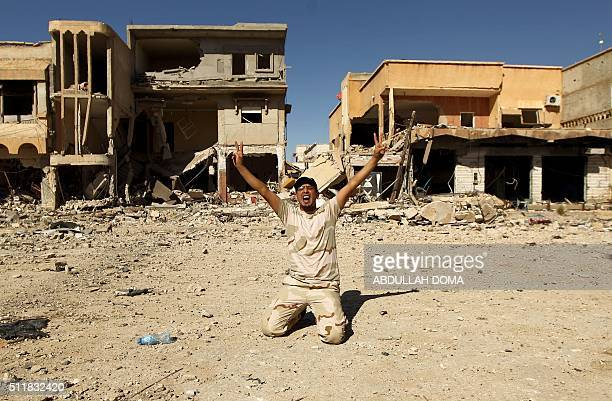 A fighter loyal to Libya's internationally recognised government celebrates in the street in Benghazi as they come close to seizing the centre of the...