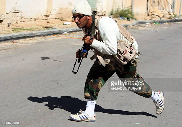 A fighter loyal to Libya's new regime the Transitional national Council runs for cover during fighting in the town of Sirte on October 12 as they...