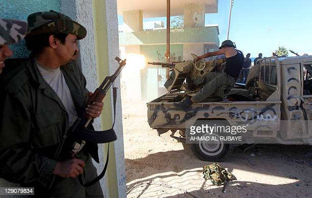 A fighter loyal to Libya's new regime the Transitional national Council looks out for comrades fire their gun during fighting in the town of Sirte on...
