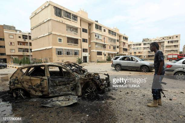 Fighter loyal to Libya's UN-recognised Government of National Accord stands next to a destroyed car following bombardment earlier in the day in the...