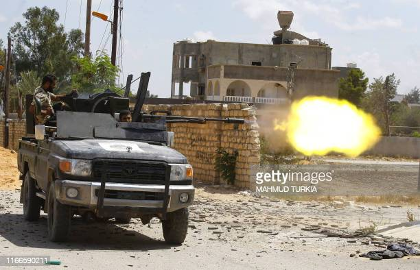 Fighter loyal to the internationally recognised Libyan Government of National Accord fires a truck-mounted gun during clashes with forces loyal to...
